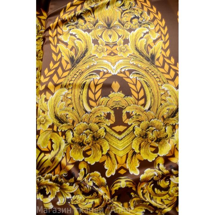 Крупные вензеля золотого цвета на темно-коричневом фоне, ткань отрезается купонами длиной 1,25-1,3 м.